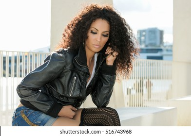 Black female, afro hairstyle, in urban background. Woman wearing denim shorts and leather jacket.