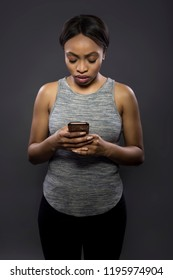 Black female athlete using a smart phone fitness app looking worried at workout data or distracted from exercising by reading text messages