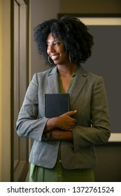 Black female businesswoman on the job training holding a manual or book.  The woman can also be a teacher or a student for an adult school at an educational institution hallway.