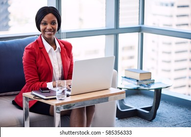 Black female businesswoman smiling at the camera while seated on a couch in a business lounge with her hands on her laptop keyboard with large windows and the cityscape behind her.