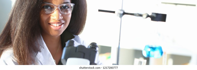 Black female chemist student conducting research using a microscope for bacterial contamination of water searching for a vaccine to treat diseases in medicine doctor concept