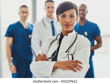 Black female doctor in front of team, looking at camera with medical team in background