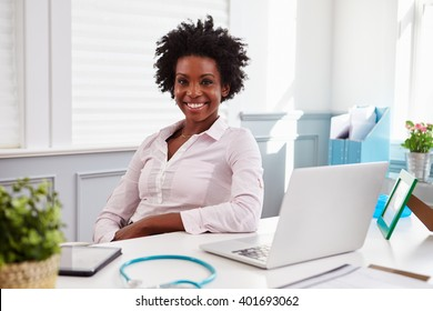 Black female doctor sits at an office desk looking to camera