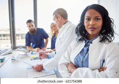 Black female doctor standing with arms crossed and looking at camera during the meeting in hospital.