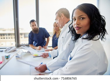 Black female doctor standing in front of medical team at hospital while attending a meeting