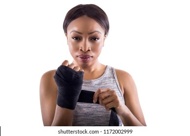 Black female fighter or boxer preparing by wearing gloves and wrapping wrist. Isolated on a white background.  She is dressed in a modest athletic outfit.  The image depicts self defense and sports.