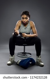 Black female fighter or boxer preparing by wearing gloves and wrapping wrist.  She is dressed in a modest athletic outfit.  The image depicts self defense and sports.
