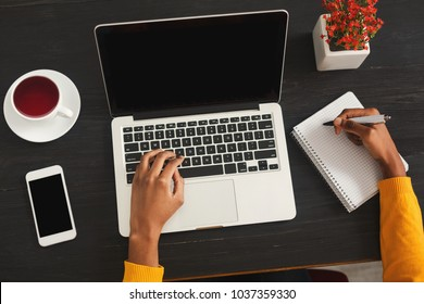 Black female hands writing in notebook and typing on laptop. Top view of african-american woman working at office desktop with smartphone. Education, business and technology concept, copy space