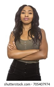 Black female isolated on a white background displaying facial confident expressions.  She is young and of African American ethnicity.