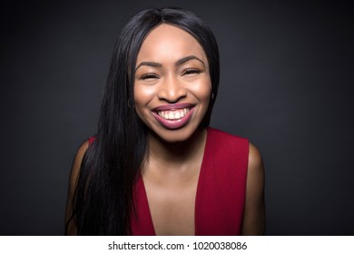 Black female model on a dark background with happy expressions.
