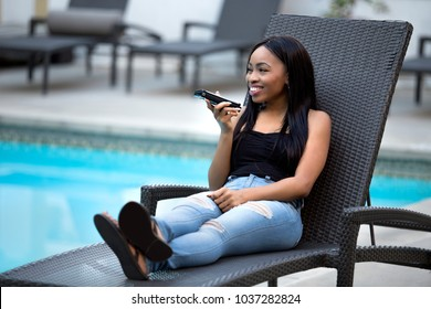 Black female on a speaker phone call in a hotel resort.  She is working while on vacation or dictating reminders on a voice assistant on her cellphone. The woman is sitting by the hotel pool.