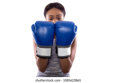 Black female on a white background wearing boxing gloves blocking gesture.  Part of image set for gritty woman series.