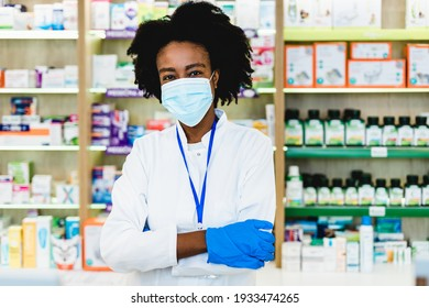 Black female pharmacist with protective mask on her face working at pharmacy. Medical healthcare, Coronavirus, Covid-19 concept.