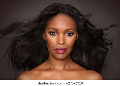 Black female portrait fashion beauty model studio photograph with hair flowing. African American woman with long hair and beautiful face.