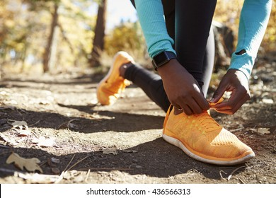 Black female runner in forest tying shoe, low section detail