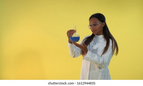 Black female scientist in lab coat looking on flask with experimental liquid on yellow background. She also has safety glasses on eyes.