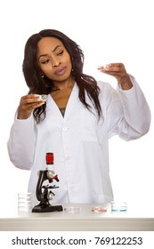 Black female scientist wearing a lab coat with microscope and petri dish doing micro biology research.  She is working in the education or medical industry.  Isolated on white background.