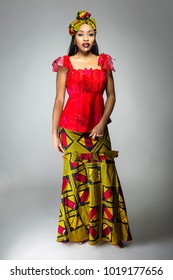 Black female showing african pride by wearing a traditional Nigerian dress and head scarf with tribal face markings or cosmetic makeup.  The costume is red and yellow and shows cultural fashion.