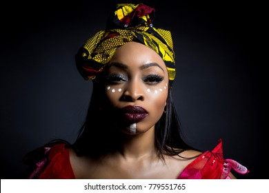 fa481a41ddf Black female showing African pride by wearing Nigerian traditional clothing  and tribal makeup or face painting