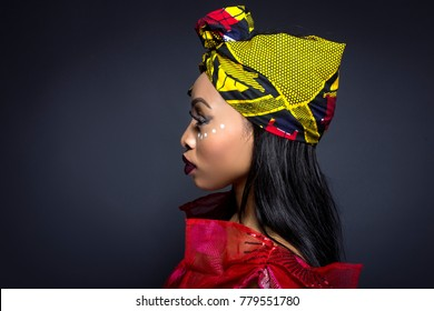 Black female showing African pride by wearing Nigerian traditional clothing and tribal makeup or face painting.  The model is shot in studio in modern vogue fashion style.