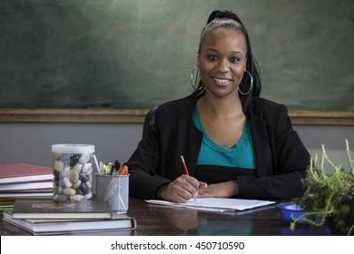 Black female teacher grading school papers
