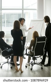 Black female team leader teaching diverse business people at meeting, multiracial executive group listening to african employee explaining new idea with flipchart at corporate training, vertical view