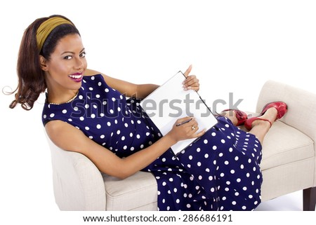 61ba5b5c3e Black female in vintage clothing writing on a diary on white background.  She is wearing