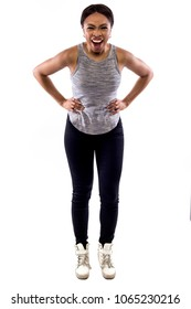 Black female wearing athletic outfit on a white background as a fitness trainer yelling or shouting