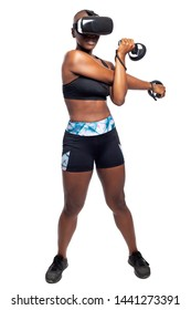 Black female wearing a virtual reality headset and holding wand controllers doing vr fitness exercises.  Gamer is in a sports simulation video game for entertainment and healthy physical activity.