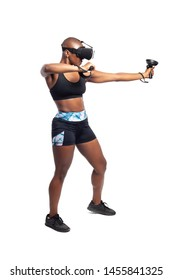 Black female wearing virtual reality headset pretending to draw a bow and playing a VR archery video game.  She is aiming at a target. Depicts esports.