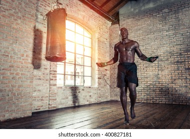 Black fighter training hard in his gym. Man using rope in an old gym,making warm up. concept about sport
