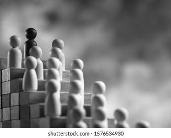 Black  Figurine Leading Human Figures On Top Of Wooden Blocks