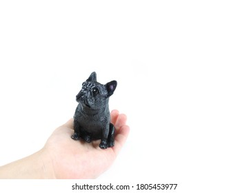 black figurine pug dog figurine on a child's palm , isolated on white background, copy space