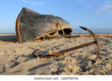 A black fishing boat lies upside down with a keel on a sandy beach. Anchor lies on the sand next to the ship.