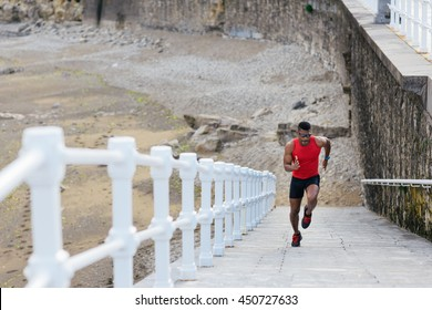Black fit runner sprinting on a ramp at the beach. Young man on running workout outdoor.