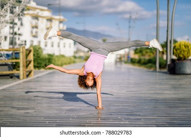 Black fit woman doing fitness acrobatics in urban background. Young female exercising and working out hard.