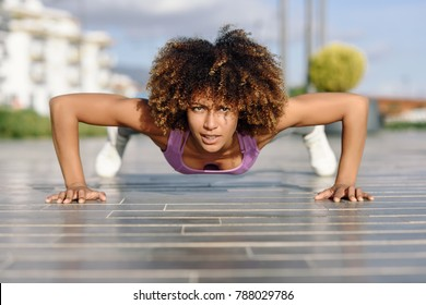 Black fit woman doing pushups on urban floor. Young female working out in the street.