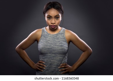 Black fitness trainer or athlete posing as a gritty woman on a dark background.  She is fit and slim.  The image depicts female sports and health.