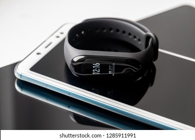 Black fitness watch (activity tracker) with with time and steps on display. Fitness tracker lies on the smartphone and tablet. Closeup, selective focus