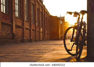 Black fixed gear bicycle in city. Bicycle parked next to sidewalk. Bicycle parked next to industrial factory.