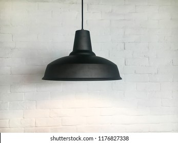 Black fixture of lamp hanging on the white bricks wall.