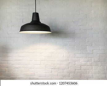 Black fixture with lamp near white brick wall background.