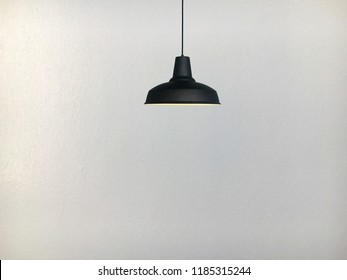 Black fixtures of lamp have the white concrete wall background.
