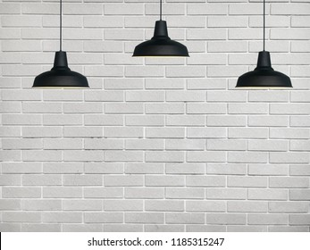 Black fixtures of lamp have the white bricks wall background.