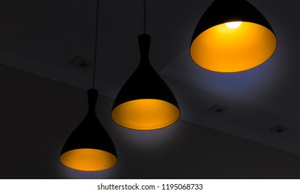Black fixtures of yellow lamp with black background  for interior design