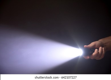 Black flashlight a beam of light directed at the viewer in male's hand isolated from right side of the frame on black background