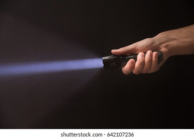 Black flashlight in male's hand isolated on black background