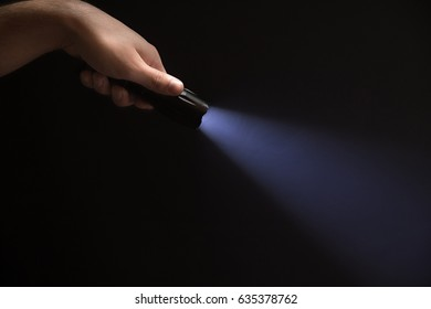Black flashlight in the man's hand coming out of the left corner of the frame, isolated on black background