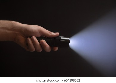 Black flashlight with wide beam in male's hand isolated from left side of the frame on black background