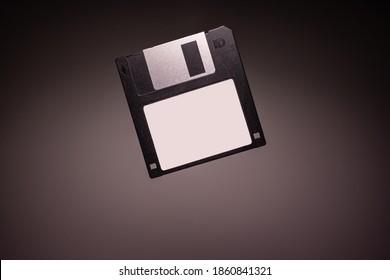 Black Floppy Diskette Levitating on Grey Background